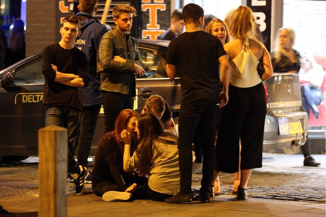 A group of youngsters sit down on the pavement after a long night out on the town in Liverpool, United Kingdom on September 21, 2016. (Photo by Paul Jacobs/FameFlynet UK)