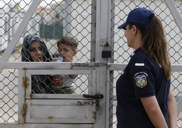 An Iraqi woman holds her baby behind the fence as a policewoman stands guard at Amygdaleza pre-departure center for refugees and migrants who are asking to return home, in Athens, Wednesday, September 21, 2016. The old migrant detention center with capacity for 300 people will be used to temporarily house those who voluntarily return to their countries. More than 60,000 migrants and refugees are stranded in transit in Greece. (Photo by Thanassis Stavrakis/AP Photo)