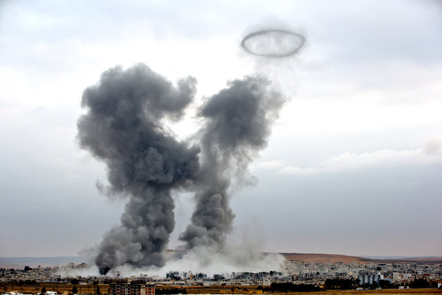 Smoke rises from the Syrian city of Kobani, following airstrikes by the US led coalition, seen from a hilltop outside Suruc, on the Turkey-Syria border Monday, November 17, 2014. Kobani, also known as Ayn Arab, and its surrounding areas, has been under assault by extremists of the Islamic State group since mid-September and is being defended by Kurdish fighters. (Photo by Vadim Ghirda/AP Photo)