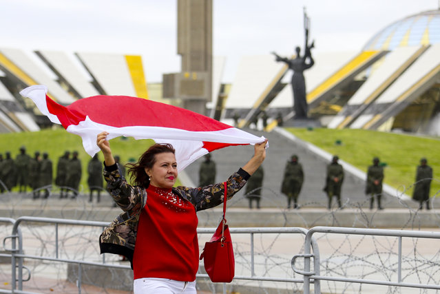 A woman waves an old Belarusian national flag as she a police line in front of a WWII memorial, during an opposition rally to protest the official presidential election results in Minsk, Belarus, Sunday, September 27, 2020. (Photo by TUT.by via AP Photo)