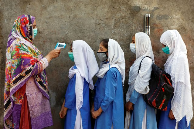 Students wear protective face masks as they have their temperature checked before entering a class, after the government allowed the reopening of schools from grade six to eight amid the coronavirus disease (COVID-19) pandemic, in Peshawar, Pakistan ob September 23, 2020. (Photo by Fayaz Aziz/Reuters)