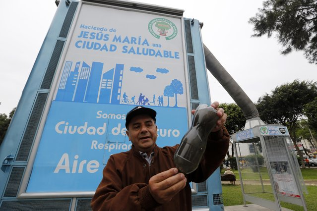 "Local inventor Jorge Gutierrez, a retired naval engineer, shows contaminants trapped by his giant air purifier, which he calls a ""super tree"", in Lima's district of Jesus Maria November 24, 2014. (Photo by Mariana Bazo/Reuters)"