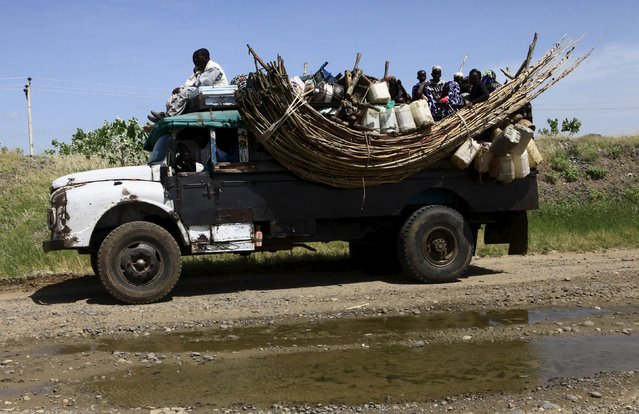Displaced people ride on a truck during a visit by a European Union delegation, at an IDP camp in Azaza, east of Ad Damazin, capital of Blue Nile state, October 21, 2015. (Photo by Mohamed Nureldin Abdallah/Reuters)