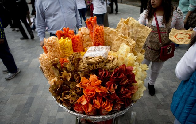 In this July 5, 2016 file photo, a street vendor sells fried snack food in Mexico City. As more states propose or approve bans on junk food sales to minors, Mexico is seeing the tide turn against high-calorie snacks that experts say have given the country one of the highest rates of childhood obesity and an unusually young coronavirus death toll. (Photo by Eduardo Verdugo/AP Photo/File)