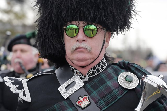 A drum major leads a bagpipe marching band during the Queens County St. Patrick's Day Parade in the Rockaway section of New York, Saturday, March 2, 2013. The ocean side community was devastated by flooding and fire during Superstorm Sandy. (Photo by Mark Lennihan/AP Photo)