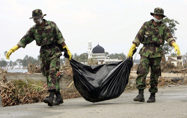 Indonesian soldiers remove a body from the village of Simpang Lima, one of thousands killed in the area, on the outskirts of Banda Aceh on the Indonesian island of Sumatra in this January 1, 2005 file photo. (Photo by Darren Whiteside/Reuters)