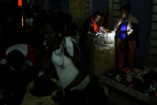 Vendors sell their goods on a street market while Hurricane Matthew approaches in Port-au-Prince, Haiti, October 2, 2016. (Photo by Carlos Garcia Rawlins/Reuters)