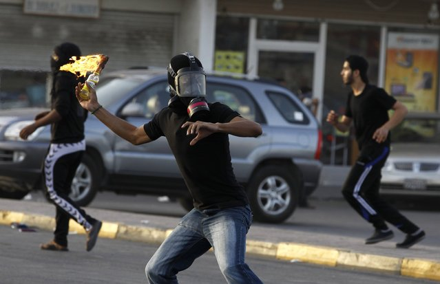 A protester throws a Molotov cocktail at riot police during clashes at an anti-government protest in the village of Diraz west of Manama, Bahrain, April 1, 2013. (Photo by Hamad I Mohammed/Reuters)