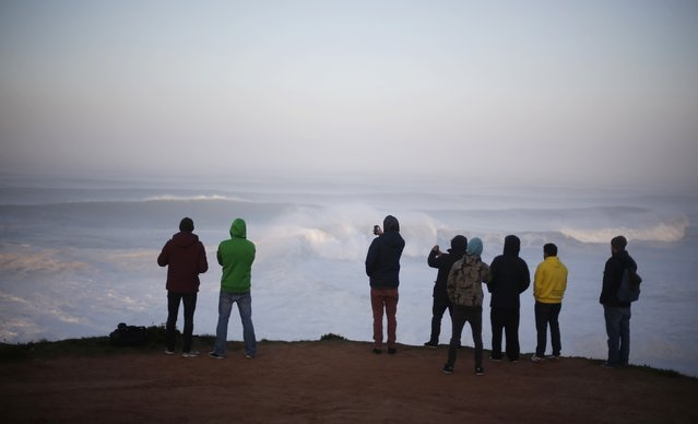 People gather to watch a tow-in surfing session at Praia do Norte, in Nazare December 11, 2014. (Photo by Rafael Marchante/Reuters)