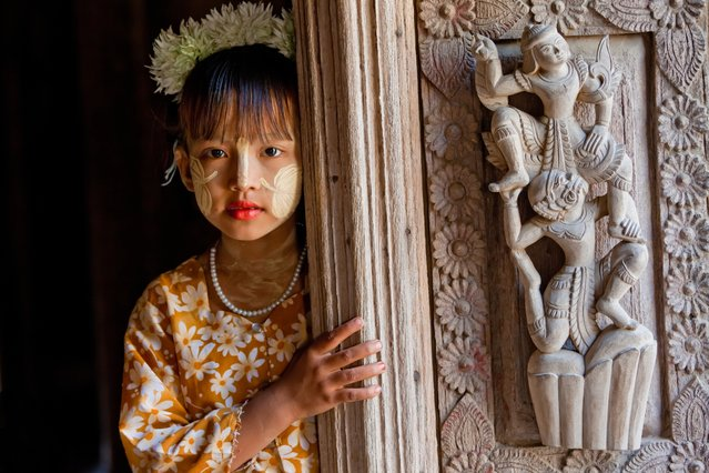 """Standing at the door of a Burmese temple a young girl wears traditional face cosmetic called thanaka painted in the shape of a leaf. Thanaka is a paste made from the bark of the thanaka tree and it is popularly used in Myanmar"". (Photo by Art Wolfe/Art Wolfe Stock)"
