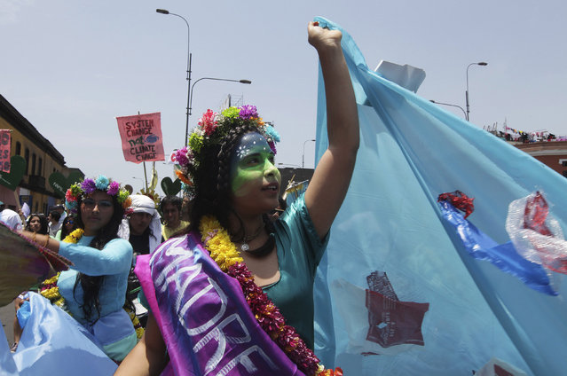 "Environmental activists march during the ""People's Climate March"" in down town Lima, December 10, 2014. Thousands marched through Lima on Wednesday to protest against climate change as the United Nations climate summit, COP20, nears its final days. (Photo by Guadalupe Pardo/Reuters)"