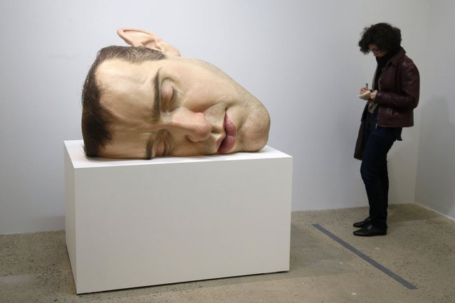 "A visitor looks at a sculpture entitled ""Mask II"" (2002) by artist Ron Mueck during the press day for his exhibition at the Fondation Cartier pour l'art contemporain in Paris April 15, 2013. (Photo by Charles Platiau/Reuters)"