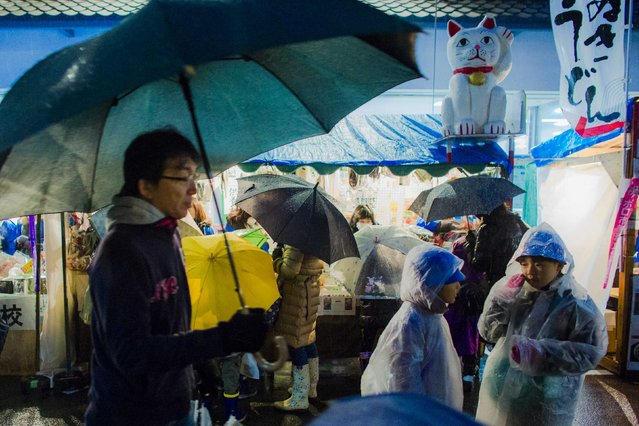 People look at goods at a stall at Boroichi flea market in Tokyo December 16, 2014. (Photo by Thomas Peter/Reuters)