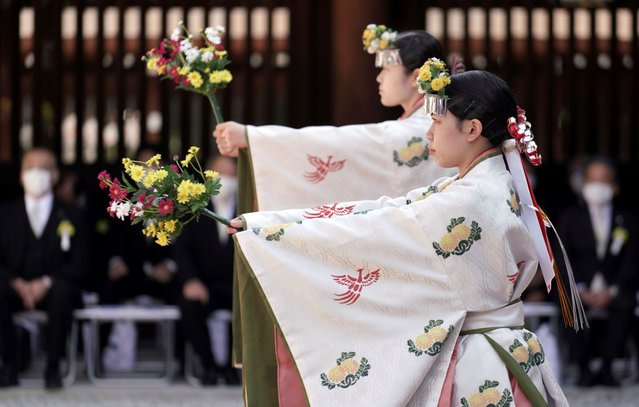 Shrine maidens in ritual clothing perform a ceremonial dance to mark the 100th anniversary of the Meiji Jingu Shinto shrine in Tokyo Sunday, November 1, 2020. Meiji Jingu, was built in 1920 to pay tribute to the Emperor Meiji and Empress Shoken. (Photo by Eugene Hoshiko/AP Photo)
