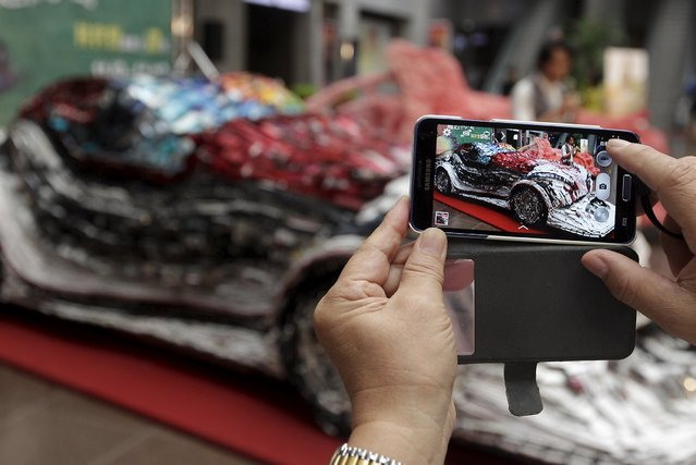 A person uses a smartphone to take a picture of an artwork by Taiwanese artist Lin Shih-pao at the Taipei City Hall, Taiwan, November 9, 2015. The art piece was built with 25,000 phones glued and nailed on a wooden frame to draw people's attention to recycling electronic waste, according to the organizer. (Photo by Pichi Chuang/Reuters)