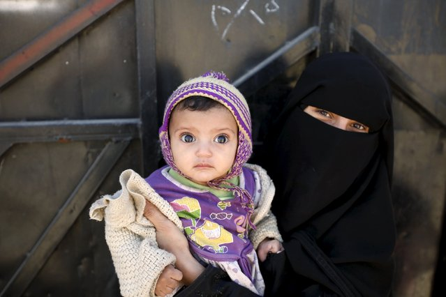 A woman holds her daughter as she waits for health workers giving polio vaccine drops during a house-to-house vaccination campaign in Yemen's capital Sanaa, November 10, 2015. (Photo by Khaled Abdullah/Reuters)