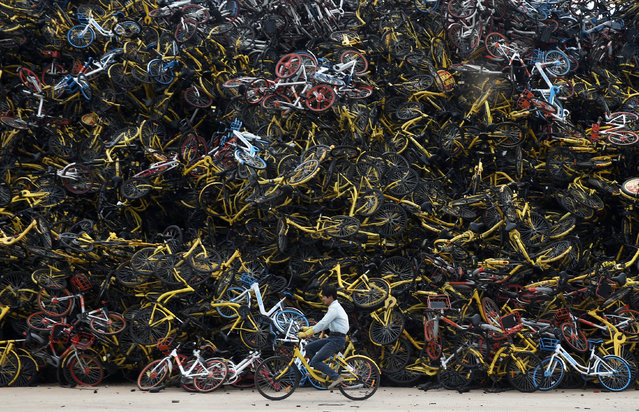 A worker rides a shared bicycle past piled-up shared bikes at a vacant lot in Xiamen, Fujian province, China, 2017. (Photo by Reuters/China Stringer Network)