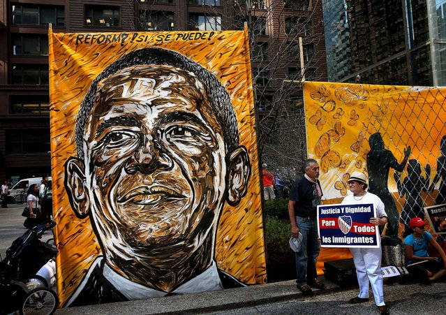 A portrait of President Barack Obama hangs in the Federal Building Plaza as demonstrators begin to gather following a May Day in Chicago. Hundreds of protestors participated in the two-mile march from the city's West side into the Loop. The majority of the marchers were protesting for immigration reform. (Photo by Scott Olson/Getty Images)