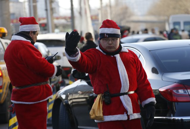 Security guards in Santa Claus costumes guide cars at a parking lot in front of a shopping mall in Beijing December 24, 2014. (Photo by Kim Kyung-Hoon/Reuters)