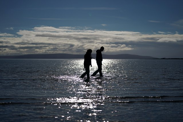 People walk along the shoreline of Ballyloughane beach searching for crabs to catch in Galway, Ireland, October 11, 2020. (Photo by Clodagh Kilcoyne/Reuters)