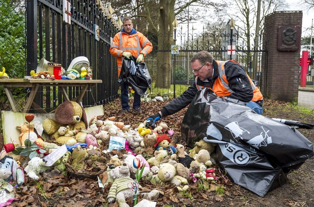 Stuffed animals are removed by municipal workers from the entrance of the Korporaal van Oudheusden barracks where the victims' bodies of the Malaysia Airlines MH17 plane crash in eastern Ukraine are identified, in Hilversum, The Netherlands, December 22, 2014. (Photo by Lex van Lieshout/EPA)