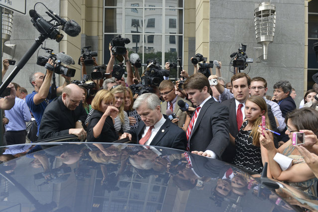 Former Governor Robert F. McDonnell wades through several members of the media after being found guilty of corruption at the Federal Courthouse in Richmond, Virginia on September 04, 2014. Former Governor Robert F. McDonnell was convicted of 11 corruption-related counts, while his wife Maureen McDonnell was convicted of eight, along with obstruction of justice. (Photo by Marvin Joseph/The Washington Post)