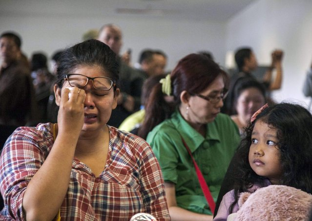 Relatives cry as they wait for news from the missing Air Asia plane at Juanda Airport, Surabaya, Indonesia, December 28, 2014. (Photo by Fully Handoko/EPA Photo)