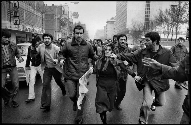 Tehran, Iran, 1979. After a demonstration in support of the constitution and prime minister Shapour Bakhtiar, a woman, believed to be a supporter of the shah, is mobbed by a revolutionary crowd. (Photo by Abbas Attar/Magnum Photos)