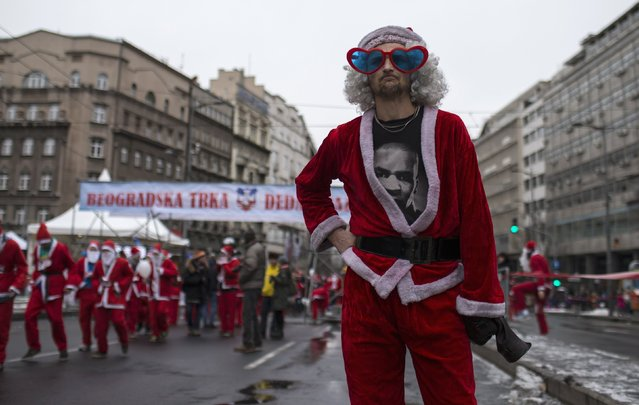A man in a Santa Claus costume waits for the start of the annual race in downtown Belgrade December 28, 2014. Serbian Orthodox believers celebrate Christmas on January 7, according to the Julian calendar. The Julian calendar is two weeks behind the Gregorian calendar. (Photo by Marko Djurica/Reuters)