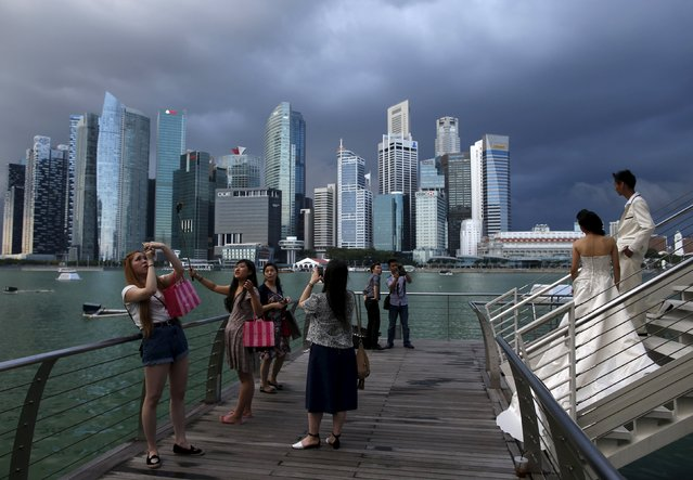Tourists and a wedding couple take photos along the Marina Bay, Singapore, March 9, 2015. (Photo by Edgar Su/Reuters)