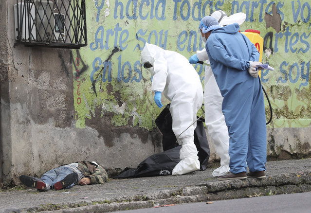 Forensic investigators look at the body of a man infected with the new coronavirus who collapsed on the street and died, according to Police Captain Diego Lopez, in Quito, Ecuador, Tuesday, May 5, 2020. (Photo by Dolores Ochoa/AP Photo)