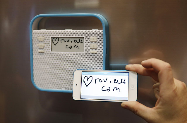A man demonstrates the messaging capabilities of the Invoxia Triby at CES Unveiled, a media preview event for CES International, Sunday, January 4, 2015, in Las Vegas. The device can make phone calls, receive digital messages and play music. (Photo by John Locher/AP Photo)