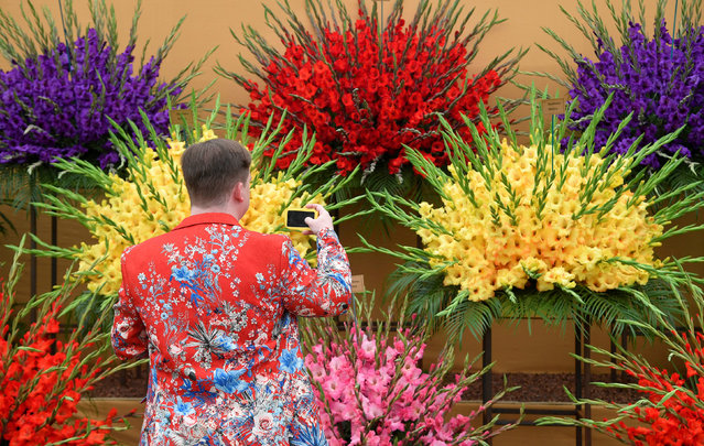 A man photographs a gladioli display at the RHS Chelsea Flower Show in London, Britain on May 21, 2018. (Photo by Toby Melville/Reuters)