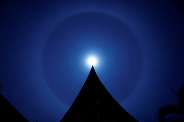 A moon ring, also called a winter halo, is seen over a Thai house at the beach on Koh Chang island, Thailand on December 30, 2020. (Photo by Jorge Silva/Reuters)