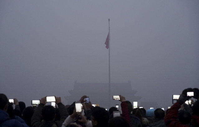 Visitors use mobile phones to take pictures and videos as they watch a flag raising ceremony at the Tiananmen Square amid heavy smog in Beijing, China, December 1, 2015. (Photo by Reuters/Stringer)