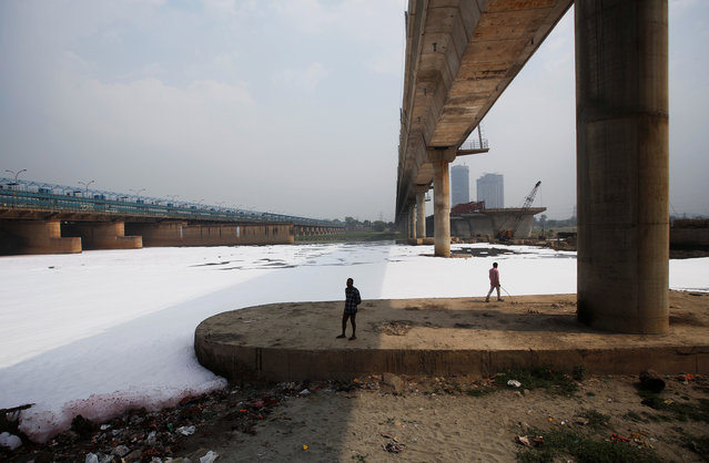 People stand under a bridge next to the polluted water of the river Yamuna, in New Delhi, India, March 21, 2018. (Photo by Adnan Abidi/Reuters)