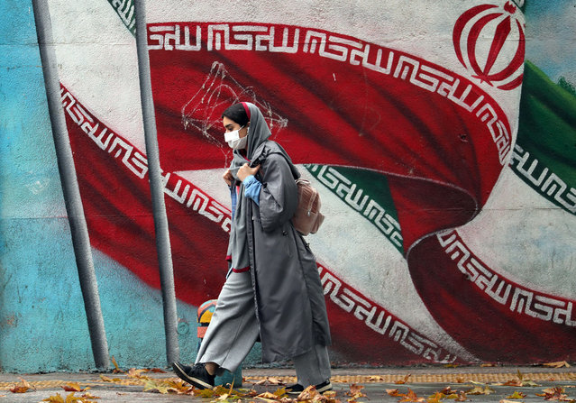 An Iranian girl walks past a mural with Iran's national flag in a street in Tehran, Iran, 03 December 2020. Iranian president Rouhani said that his government does not agree with the parliament's draft bill to quit the nuclear deal, to reduce nuclear commitment and to increase nuclear activities. The development comes after the assassination of Iranian nuclear scientist Mohsen Fakhrizadeh earlier this week. (Photo by Abedin Taherkenareh/EPA/EFE/Rex Features/Shutterstock)