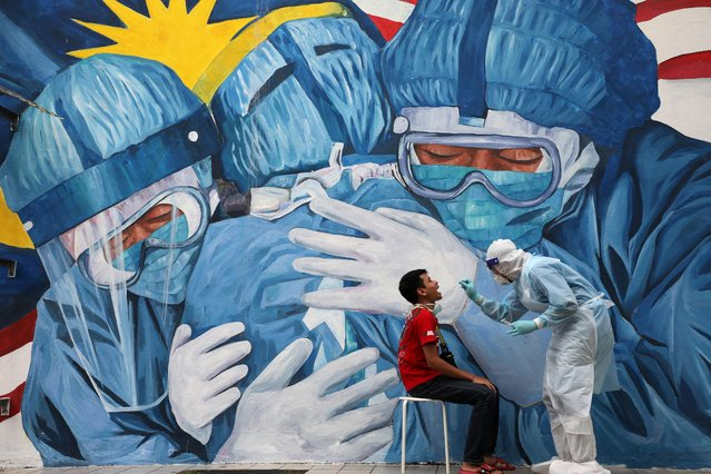 A doctor collects a swab sample from a man to be tested for the coronavirus disease (COVID-19) outside Clinic Ajwa in Shah Alam, Malaysia on December 10, 2020. (Photo by Lim Huey/Reuters)