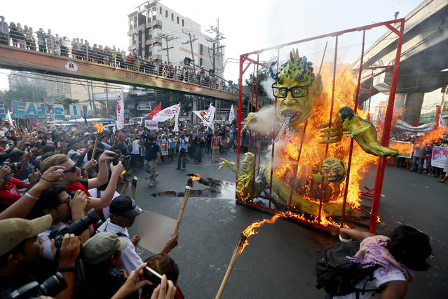 Protesters burn a giant effigy of Philippine President Benigno Aquino III and small ones of some members of his Cabinet inside a mock jail during a rally near the Presidential Palace in Manila to mark the 67th anniversary of the adoption of the Universal Declaration of Human Rights Thursday, December 10, 2015. The protesters accused the government for committing human rights violations by the military and paramilitary groups. (Photo by Bullit Marquez/AP Photo)