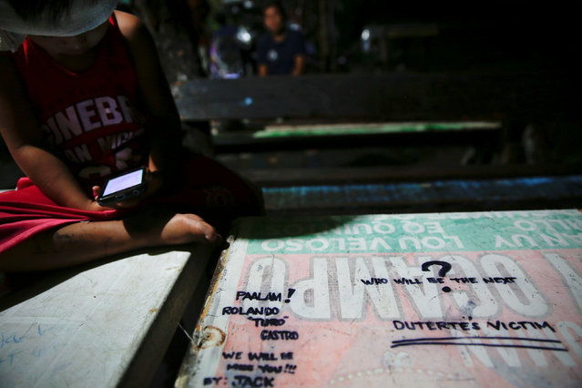 """A message reading """"Who will be the next Duterte's victim"""" is written on a table as people gather for the wake of a man who was, according to police report, killed in a drugs buy-bust operation, in Manila, Philippines November 2, 2016. (Photo by Damir Sagolj/Reuters)"""