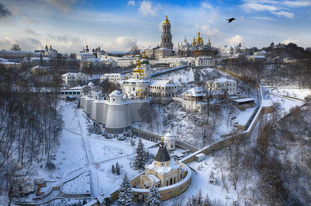 A bird flies over the sky near the 1000-year old Orthodox Monastery of Caves covered with the first snow this winter in Kyiv, Ukraine, Friday, January 15, 2021. Ukraine has been hit with unusually cold weather with temperatures of 21 degrees Celsius below zero (69.8 F). (Photo by Efrem Lukatsky/AP Photo)