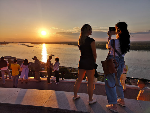 In this Friday, June 8, 2018 filer, people watch the sunset over the river Wolga during the 2018 soccer World Cup in Nizhny Novgorod, Russia. (Photo by Michael Sohn/AP Photo)