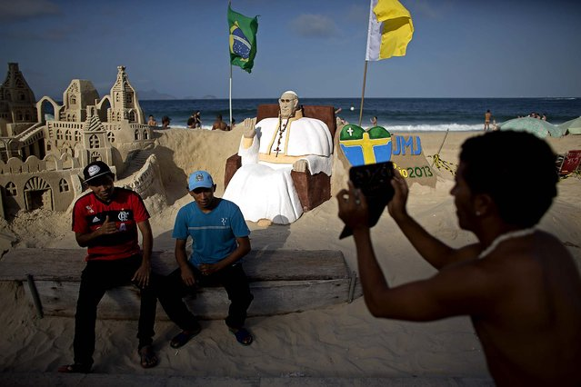 Two men have their picture taken next to a sand sculpture that resembles Pope Francis in Copacabana beach, Rio de Janeiro, on July 21, 2013. Pope Francis, the 76-year-old Argentine who became the church's first pontiff from the Americas in March, will return Monday to the embrace of Latin America to preside over the Roman Catholic Church's World Youth Day festival in Brazil. (Photo by Victor R. Caivano/Associated Press)