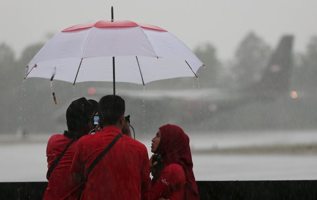 TV crew members take cover from heavy downpour as Indonesia Air force plane CN235 takes off at the airport in Pangkalan Bun, Monday, January 5 2015. (Photo by Tatan Syuflana/AP Photo)