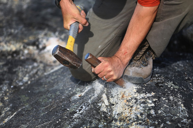 Jason Briner, with the University of Buffalo, uses a hammer and chisel to gather samples of granite to research the age of the local glacial retreat, on July 24, 2013 near Ilulissat. (Photo by Joe Raedle/Getty Images via The Atlantic)