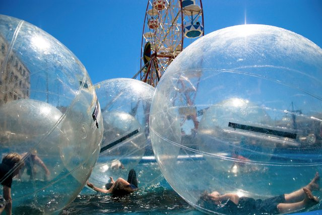 Children float in plastic bubbles at an amusement park in Cape Town, South Africa. (Photo by Philip Grube)