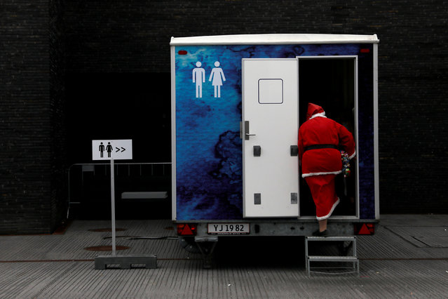 A person dressed as Santa Claus uses a restroom during the World Santa Claus Congress, an annual event held every summer in Copenhagen, Denmark, July 23, 2018. (Photo by Andrew Kelly/Reuters)