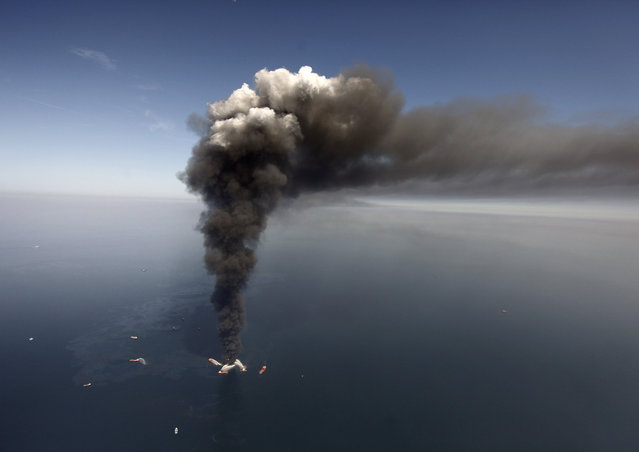 In this Wednesday, April 21, 2010 file photo, oil can be seen in the Gulf of Mexico, more than 50 miles southeast of Venice on Louisiana's tip, as a large plume of smoke rises from fires on BP's Deepwater Horizon offshore oil rig.  Legal battles arising from the 2010 Gulf of Mexico oil spill play out in two federal courts this coming week.  On Monday, February 2, 2015, trial resumes in a federal district courtroom where BP and a minority partner in its ill-fated Macondo well are trying to fend off billions in Clean Water Act penalties. (Photo by Gerald Herbert/AP Photo)