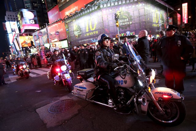 Members of the New York Police Department ride their motorcycles through the crowd during New Year celebrations in Times Square in the Manhattan borough of New York December 31, 2015. (Photo by Andrew Kelly/Reuters)