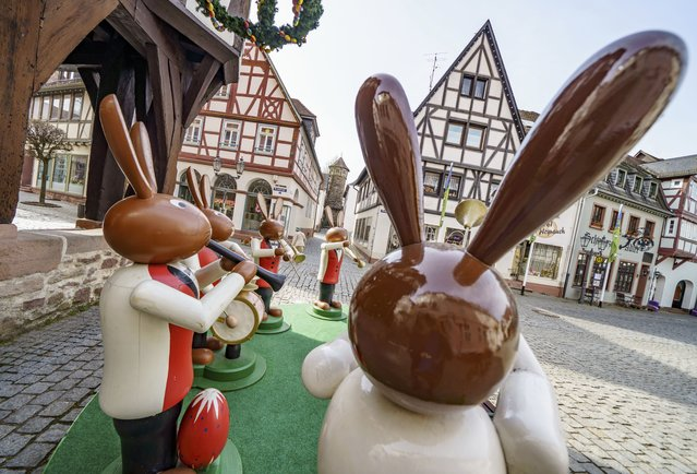 Human-sized wooden figures representing Easter bunnies playing music stand in front of Michelstadt's historic town hall, as they do every year, to spread Easter atmosphere in Michelstadt, Germany, Thursday, April 1, 2021. However, the popular meeting place in the heart of the town in the Odenwald was almost deserted on Thursday morning due to the pandemic. (Photo by Frank Rumpenhorst/dpa via AP Photo)